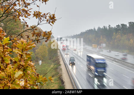 The highway A3 near Nuremberg with many cars with lights switched on driving with speed on a rainy day in wet conditions in  November with autumn fore - Stock Photo