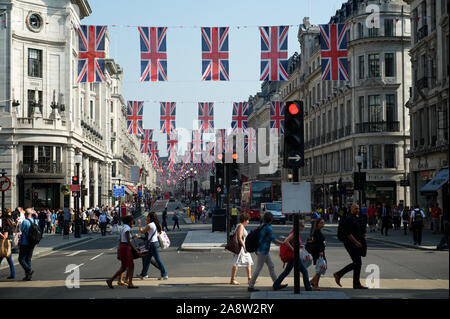 LONDON - MAY 24, 2012: British Union Jack flags decorate a busy intersection full of pedestrians in the Regent Street shopping district. - Stock Photo