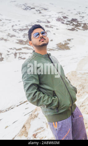 Close up portrait of a happy Indian man wearing winter jacket and sunglasses, standing in leh ladakh region in winter. Mountain and snow background. - Stock Photo