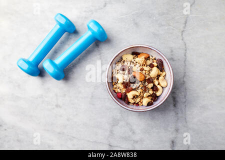 Bowl of granola with milk, nuts, raisins and cranberries. Blue dumbbells in background. - Stock Photo