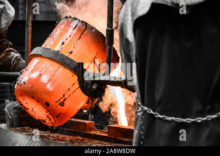 In a foundry workshop. The molten metal is poured into a mold from a crucible maneuvered by two workers - Stock Photo