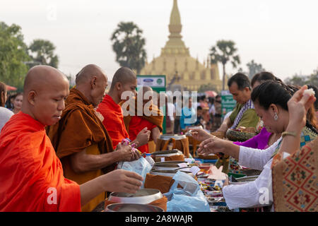 Vientiane, Laos. 11th Nov, 2019. People attend the almsgiving activity around the That Luang Stupa in Vientiane, capital of Laos, Nov. 11, 2019. Considered as the most important religious festival in Laos, the That Luang Festival, which falls from Nov. 5 to Nov. 11 this year, concluded on Monday with a mass almsgiving activity held in and around the That Luang Stupa in Vientiane. Credit: Kaikeo Saiyasane/Xinhua/Alamy Live News - Stock Photo
