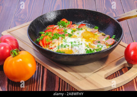 Scrambled eggs with tomatoes, sausages, sweet pepper and sprinkled with chopped parsley in a frying pan - Stock Photo
