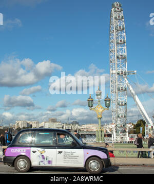 London Eye and a London taxi seen on Westminster bridge, London, England, UK on a fresh but sunny day in early November. - Stock Photo