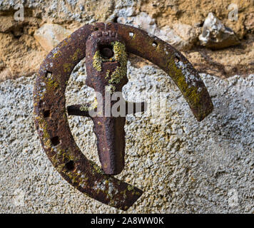 Old rusty horse shoe hanging on exterior wall in rural France - Stock Photo