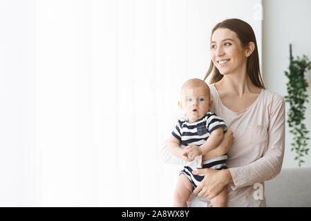 Happy mother holding newborn baby and looking out the window - Stock Photo