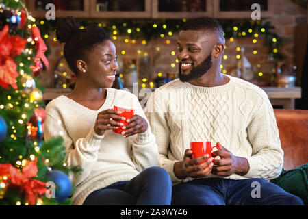Smiling afro couple drinking hot chocolate, celebrating Cristmas at home - Stock Photo