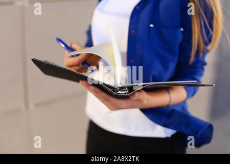Girl holds in hands diary, notebook with sheets and pen and leafs through pages. - Stock Photo