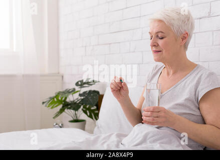 Healthy senior woman holding pills and glass of water - Stock Photo