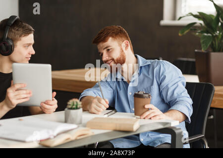 Smart student helping his classmate with homework - Stock Photo