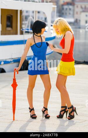 Blonde and black-haired attractive teenagers smile happy smiling sunny after rain umbrella in hand beauty beauties wearing innocent curiosity curious - Stock Photo