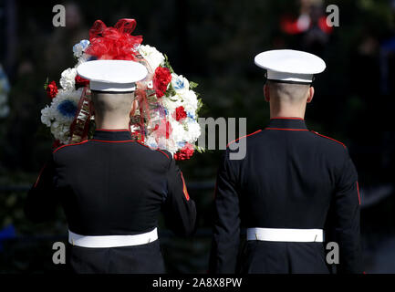New York, USA. 11th Nov, 2019. A United States Marine walks with a wreath after President Donald Trump delivers remarks before a wreath laying during the Opening Ceremony of the 100th annual New York City Veterans Day Parade. The New York City Veterans Day Parade is a non-partisan, non-political event to honor the service of vets and salute currently-serving military, dubbed 'the largest commemoration of service in the nation'. Over 25,000 people participate, including vets, active duty military personnel, and high school and college bands and floats. Credit: UPI/Alamy Live News - Stock Photo