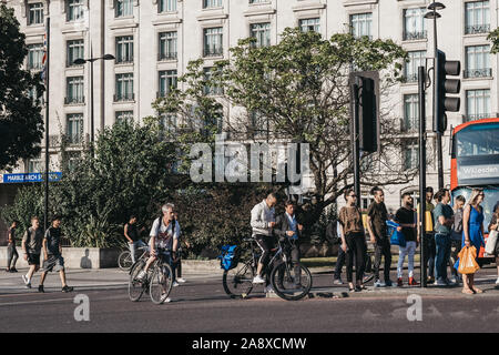 London, UK - July 18, 2019: Pedestrians and cyclists waiting to cross the road next to Marble Arch, London, an area name after 9th-century white marbl - Stock Photo