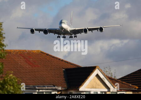 Qatar Airways Airbus A380 A7-APD flying low over the rooftops at London Heathrow Airport, UK - Stock Photo