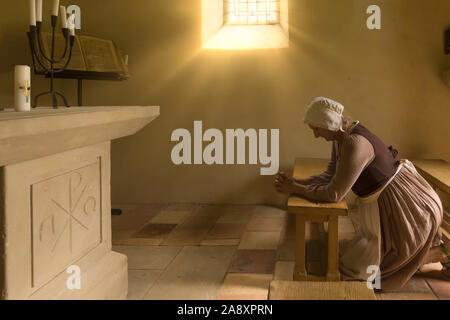 Mature woman in medieval outfit kneeling in prayer in the chapel of a French medieval castle - Stock Photo