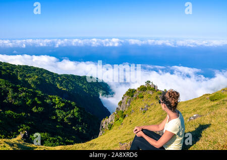 Female traveller sitting on the top of the hill has an amazing view of the landscape in Madeira, Portugal. Rocky hills and forest, blue Atlantic Ocean in background. Above the clouds. Travel concept. - Stock Photo