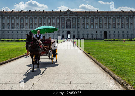An horse carriage in front of Caserta Royal Palace riding the tourists to discover the park. Caserta, Campania, Italy, October 2019 - Stock Photo