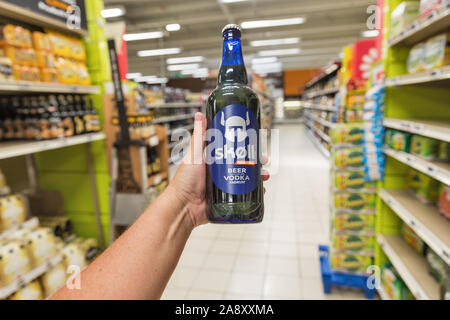 ALERIA, CORSICA, FRANCE - JULY 17, 2019: White man's hand holds a Skoll beer with vodka in E.Leclerc supermarket. Corsica is located southeast of the - Stock Photo