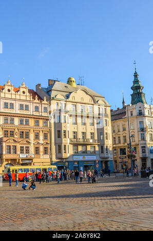 Plzen, Czechia - Oct 28, 2019: People on the main square, Republic Square, in Pilsen, Bohemia, Czech Republice, Historical houses in the background. Old center, sunny day. Daily life, city street. - Stock Photo