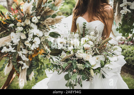 Woman holding in hands big wedding bouquet in Boho style. Dried flowers, white roses and orchids, bird feathers in decor. Floristic concept. - Stock Photo