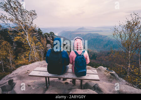 Young couple in outdoor clothing with backpacks sitting and rest on bench enjoying view of mountain ridge, forest and river in the valley on hiking
