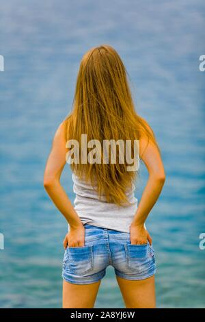 Teen girl standing view from back hands in pockets - Stock Photo