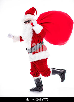 Santa Claus carrying sack full of gifts - Stock Photo