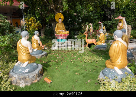 A circle of Buddhist monk sculptures pray around a statue of Buddha in Nha Trang, Vietnam - Stock Photo