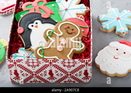 Christmas sugar and gingerbread cookies decorated with royal icing in a box or tin - Stock Photo