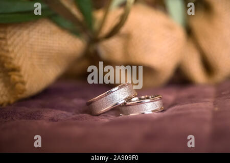 Beautiful toned picture with wedding rings lie on a surface against the background - Stock Photo
