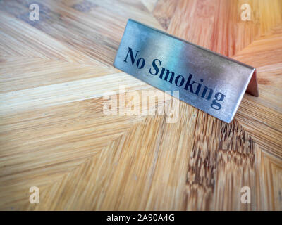No smoking sign on wooden table. Warning sign, text 'no smoking'  on silver metallic style plate sign. - Stock Photo