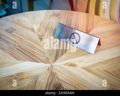 No smoking sign on wooden table. Warning sign, no smoking icon on silver metallic style plate sign. - Stock Photo