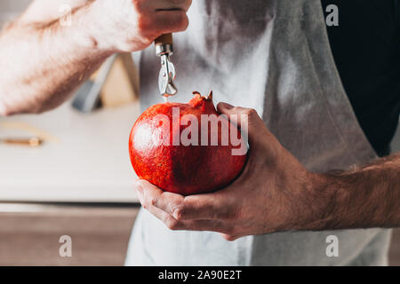How to peel a pomegranate - a concept - a man tries to peel a pomegranate with a can opener - Stock Photo