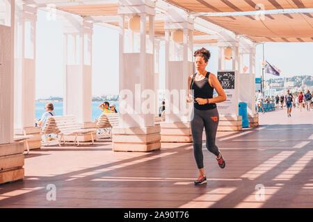 Nice, Provence / France - September 29, 2018: Young slim sporty woman runs along the promenade - Stock Photo