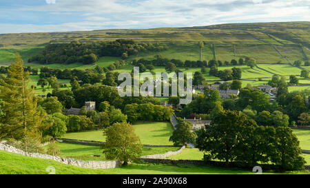 Summer evening sunlight on picturesque Dales village (church & houses) nestling in valley under upland hills - Arncliffe, North Yorkshire, England, UK