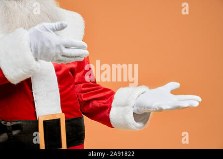 Close up of Santa Claus hands in white gloves with open palms and empty space posing in studio with orange background. Place for text or advertisement of some product. - Stock Photo