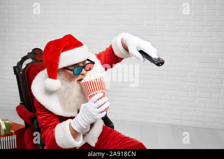 Happy authentic Santa Claus in 3d glasses, sitting in cozy chair while watching TV and eating tasty popcorn from striped bucket. Mature man relaxing after hard working day - Stock Photo