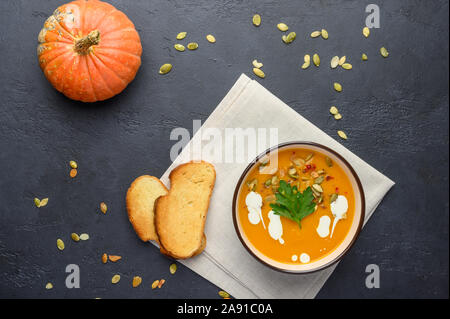 Healthy organic pumpkin cream soup with cream, croutons, seeds and basil on a dark wooden background - Stock Photo