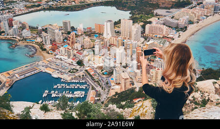 Girl climbed up on Penon de Ifach rock. Enjoy view of city from top, stand on peak of mountain takes photo of cityscape and scenery. Tourism concept - Stock Photo