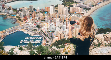 Woman climbed up on Penon de Ifach rock. Enjoy view of city from top, stand on peak of mountain takes photo of cityscape and scenery. Tourism concept - Stock Photo