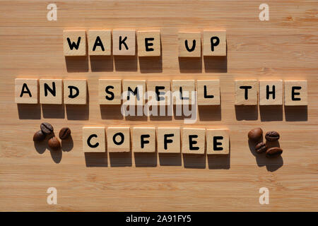 Wake Up And Smell The Coffee in 3D wooden alphabet letters with roasted coffee beans on a bamboo wood background - Stock Photo