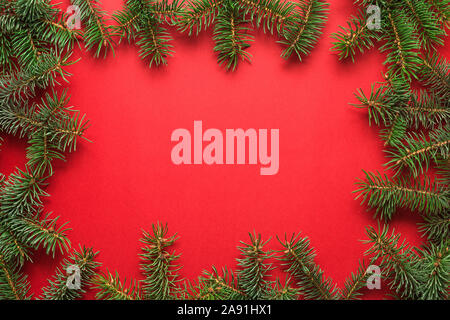 Christmas background. Frame made of fir tree branches on red background. Flat lay. top view with copy space - Stock Photo