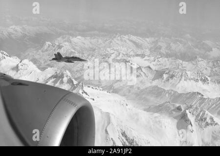 FA-18 military jets from Swiss Airforce escorting civil airplaine in the swiss alps - Stock Photo