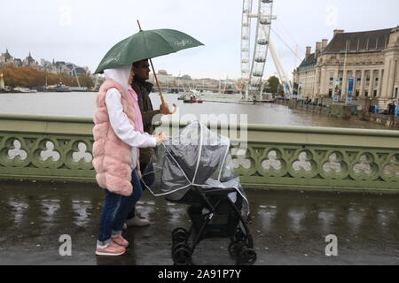Westminster London, UK. 12 November, 2019. Pedestrians brave the  rain on Westminster Bridge on a cold autumnal day in London . Credit: amer ghazzal/Alamy Live News - Stock Photo