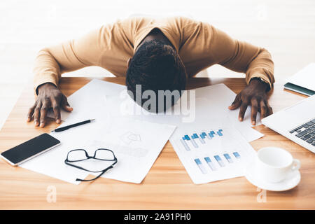 Stressed afro businessman with head down on the table