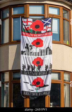 Large Lest we forget flag banner hanging from house on Remembrance Sunday in Southend on Sea, Essex, UK. Home, remembering - Stock Photo