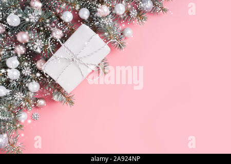 Christmas pastel composition with white gift on pink background. Xmas frame with space for text. View from above. Flat lay style. - Stock Photo
