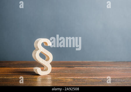 A wooden paragraph figurine. Justice and judicial system concept. Legal assistance, services of lawyers. Democratic institutions, human rights and pro - Stock Photo