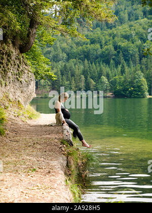 Beautiful, cute pregnant woman sits near a mountain lake in a forest on the shore - Stock Photo