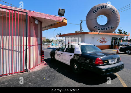 Police car in front of legendary donut snack 'Randy 's Donut' in the district Inglewood, Los Angeles, California, USA - Stock Photo